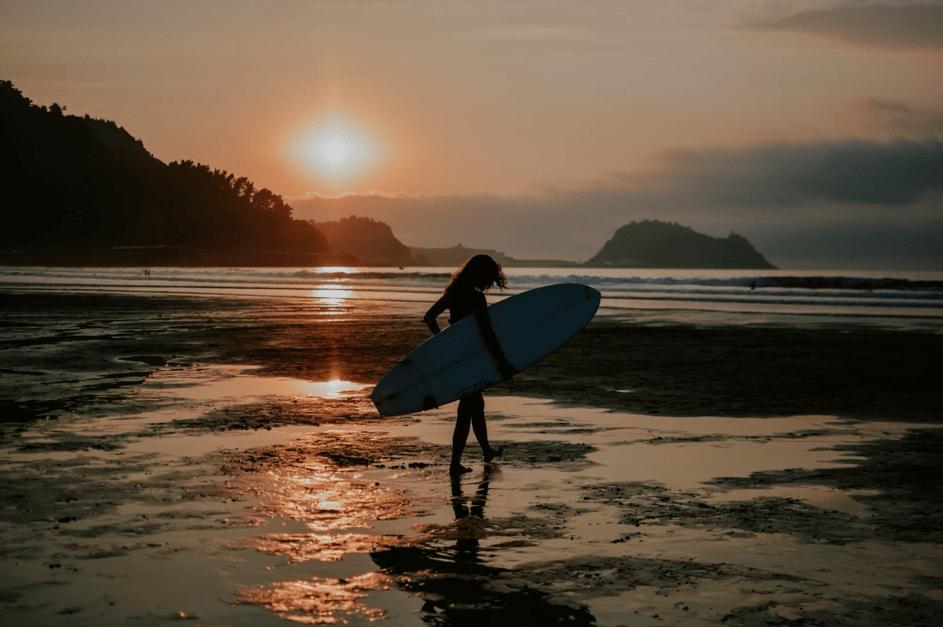 surferka - dziewczyna z deską surfingową o zachodzie słońca
