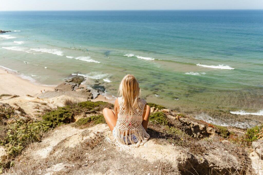 dziewczyna na klifie ogląda piękny widok na ocean